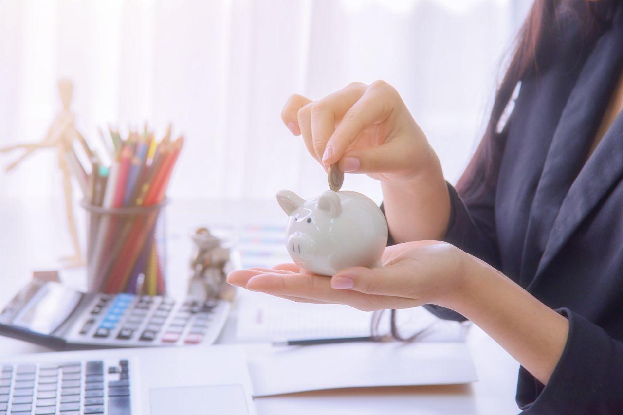 Woman putting savings inside a piggy bank