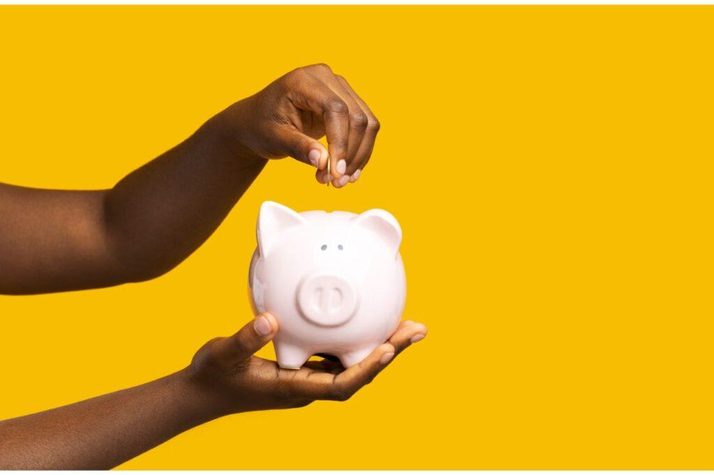 A hand putting coins inside a piggy bank
