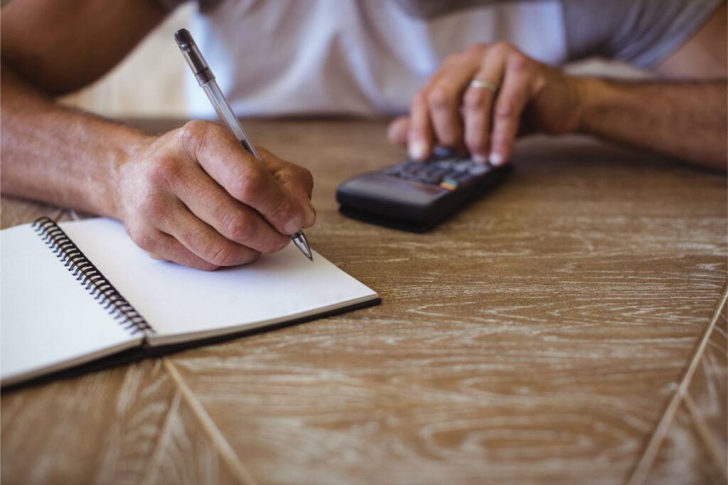Man keeping track of his expenses on a notebook